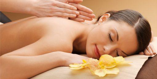 woman having facial or body massage in spa salon